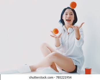 Asian beautiful woman with orange fruit happy good mood on white background