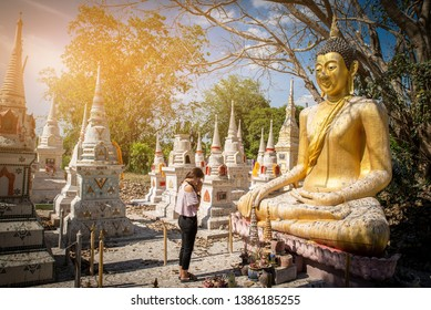 asian beautiful woman to pay respect to Buddha statue  under big tree with many old pagoda in thai temple