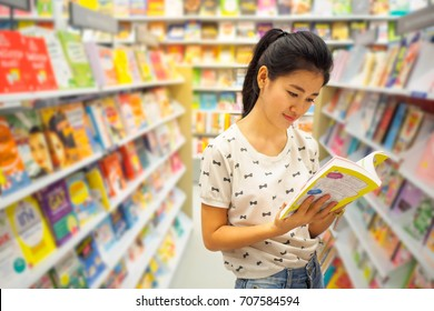 asian beautiful woman reading a book at bookshop