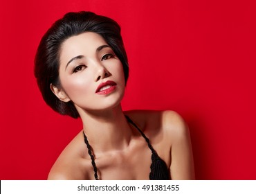Asian beautiful woman with red lipstick isolated on red background. copyspace.