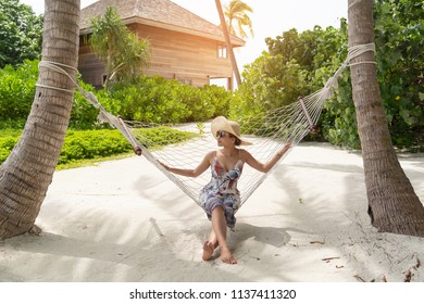 Asian beautiful woman relaxing on hammock coconut in garden resort background, vacation holiday concepts with tropical Maldives island background.
