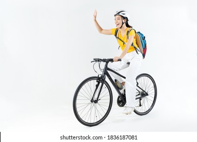 Asian beautiful woman, she is riding a city bike to work.She is greeting.studio concept