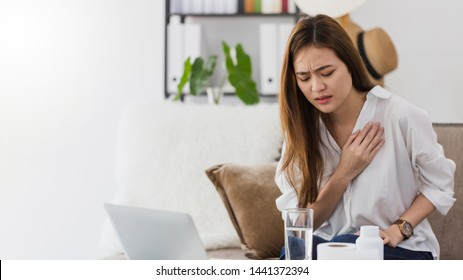 Asian beautiful woman sick with feeling pain in the chest while working with a laptop.Hand holding chest after taking a  medication.Concept of hard work without maintaining health.