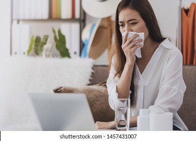 Asian beautiful woman sick with the flu while working with a laptop.Hand holding tissue paper after taking a cold medication.Concept of hard work without maintaining health.