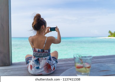 Asian beautiful woman take photo with smartphone, vacation holiday concepts with tropical Maldives island background.