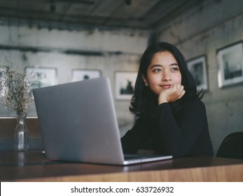 Asian beautiful woman thinking idea with laptop computer in coffee shop
