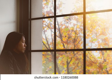 Asian beautiful woman thinking  and standing in room with autumn leaf outside window background.Concept of foreign students homesick.