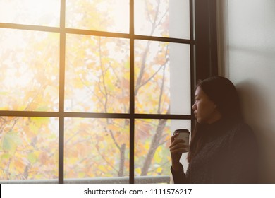 Asian beautiful woman thinking while drink coffee and standing in room with autumn leaf outside window background.Concept of foreign student homesick.