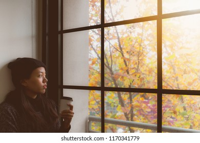 Asian beautiful woman thinking while drink coffee and standing in room with autumn leaf outside window background.Concept of foreign students homesick.