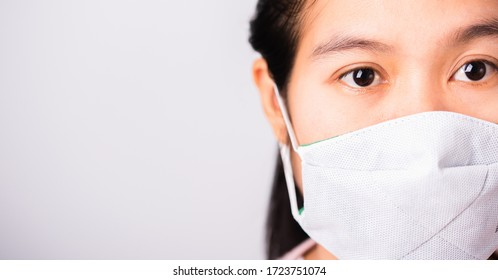 Asian beautiful woman wearing protection face mask against coronavirus her looking to camera, studio shot isolated on white background with copy space, COVID-19 or corona virus concept