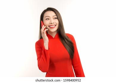Asian beautiful woman wearing vietnamese dress is talking on her mobile phone