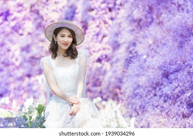 Asian beautiful woman in white dress wears a white hat and sit among purple flower garden in happily moment.