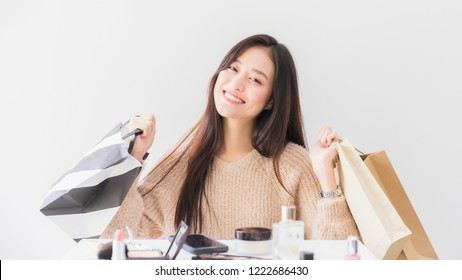 Asian beautiful women blogger smiling and holding shopping bag in the white room with cosmetics on table.Concept of online shopping business.