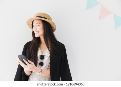 Asian beautiful women blogger are using the smartphone live streaming online with hat and sunglasses in the white room with flag decoration.Concept of online shopping business.