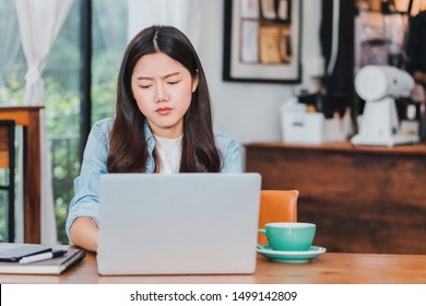 Asian beautiful young businesswoman feeling worry and stress in coffee shop and cafe background with laptop and coffee cup on wood table.Concept of inconvenience to use online technology.