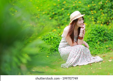 Asian beautiful young girl,wear floral maxi dress and hat, sitting on the ground at spring