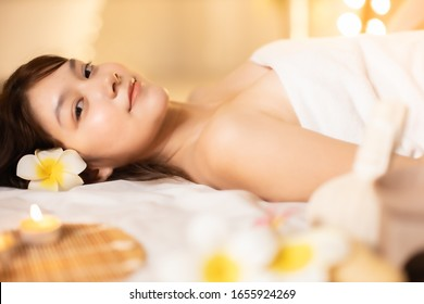 Asian Beautiful, young and healthy woman in spa salon. Massage treatment spa room  . Traditional medicine and healing concept.closed up face