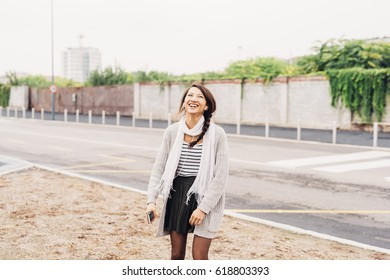 Asian beautiful young woman outdoor in the city listening music with earphones and smart phone hand hold - relaxing, music, enjoying concept
