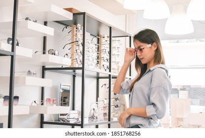 Asian beautiful young woman shopping and trying glasses in store. Sales, Discount and Optical Concept.