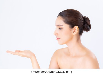 Asian beautiful young woman showing with healthy clean skin presenting something empty copy space on the hand isolated on white background, beauty concept.