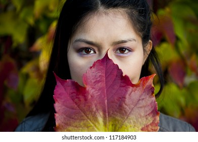 asian beauty behind a colorful maple leaf