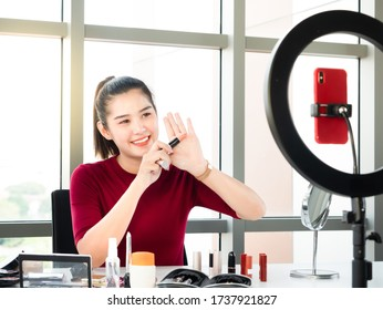 Asian beauty blogger or makeup artist woman review pink lipstick color show on her hand while record live through smartphone with selfie ring light for share on social media or channel in home studio