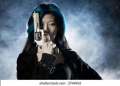 Asian beauty holding gun with smoke
