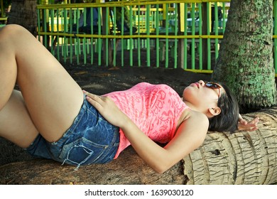 Asian beauty laying on a tree on a tropical beach