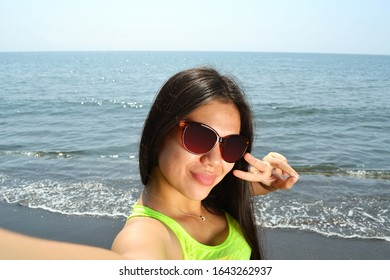 Asian beauty making duck face taking a selfie with the sea behind