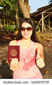 Asian beauty on the beach with a travel document and thumb up sign