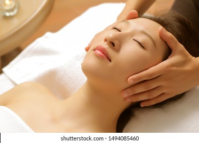 Asian beauty is receiving facial treatment from a beautician