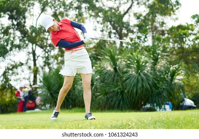Asian beauty swinging a golf club in course