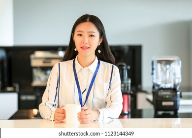 Asian beauty white collar worker holding cup in tea bar in office area