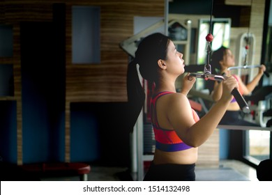 Asian beauty woman doing exercise for back. Working out on a lat pulldown machine. Diet, weight loss, slim body, healthy lifestyle concept.