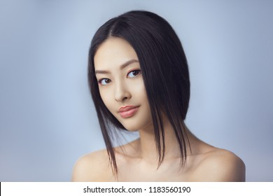 Asian beauty woman skin care close-up. Beautiful young girl with perfect skin face looking at camera. Isolated on gray background. Tender smiling mixed race Asian Caucasian female in studio. Fashion
