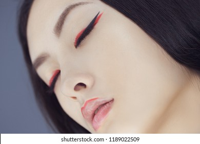 Asian beauty woman skin care close-up. Beautiful young girl with perfect skin face looking with closed eyes. Isolated on gray background. Tender sensual mixed race Asian Caucasian female in studio