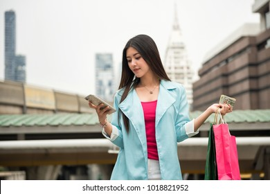 Asian beauty young female traveler shop in city with money banknotes, US dollar bills, and check store information from smart phone or mobile phone with modern town background and copy space for text.