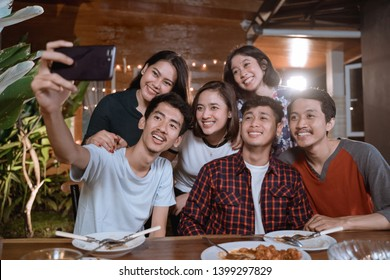 asian bestfriend group take selfie with smartphone while having garden party dinner together