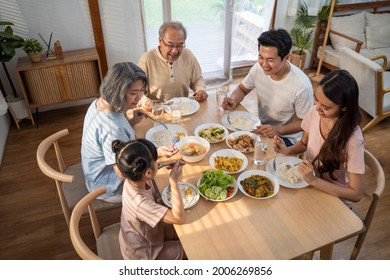 Asian Big happy family spend time have lunch on dinner table together. Little kid daughter enjoy eating foods with father, mother and grandparents. Multi-Generation relationship and activity in house - Shutterstock ID 2006269856