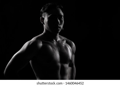 Asian Big Muscle Fitness Man exercise show arms, bicep, chest with sweat from heat. Young Sport Male six packs shoot in low key lighting exposure with shadow contrast, copy space