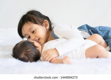 Asian big sister is hugging and talking with her infant little brother with love, concept of love and relation between sibling in the family.