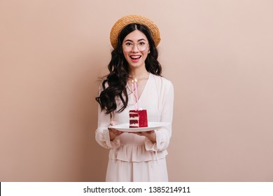 Asian birthday girl looking at camera with smile. Happy japanese woman in straw hat holding cake.