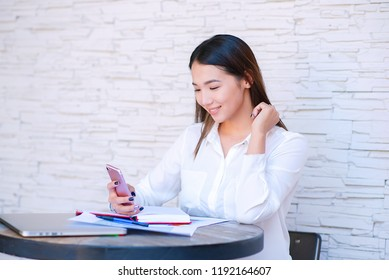 Asian bisiness woman dialing number on cellphone using good internet connection indoors. Kazakh female puzzled on watching video in social networks via cellular while sitting in cafe.
