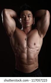 Asian Body Builder Posing flexing looking at the camera