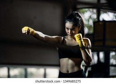 Asian boxing girl in fighting action at the gyms. A smart and healthy girl is ready to fight with boxing skill. Show the commitment in her eyes and strong muscle of her body.