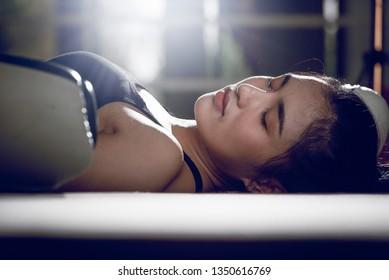 ฺ Asian boxing girl is prostrating on the boxing state after the fight.