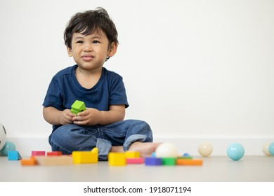 An Asian boy about 1 year old. Playing in the living room in the house He plays wooden toys in different colors. He is wearing a blue shirt.
