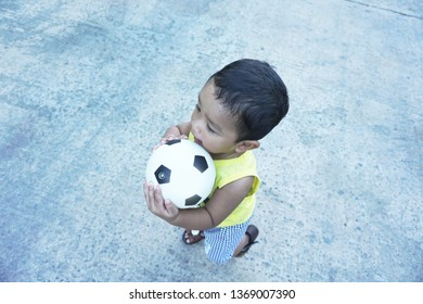 Asian boy aged 1 year 3 months playing football and bicycles outside the house