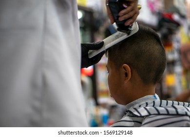 An Asian boy in the barbershop and doing hair cutting