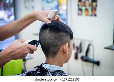 An Asian boy in the barbershop  ,Boy getting haircut by barber in barbershop
